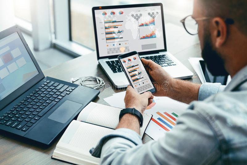 Modnisia mężczyzna siedzi w kawiarni, używa smartphone, pracuje na dwa laptopach z mapami, wykresy, diagramy na ekranie Online ma obrazy royalty free