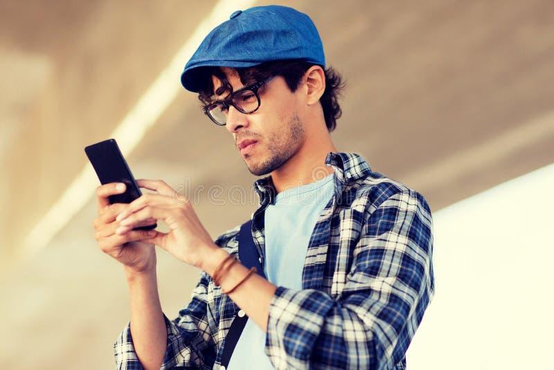 Modnisia mężczyzna texting wiadomość na smartphone zdjęcie royalty free