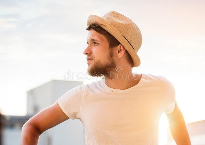 Modnisia mężczyzna w kapeluszu i koszulce na plaży, pogodny lato obrazy royalty free