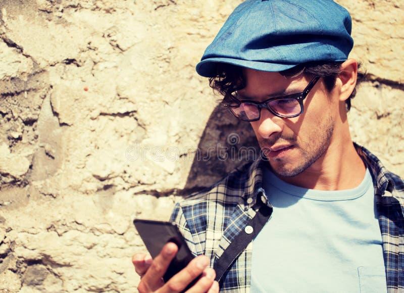 Modnisia m??czyzna texting wiadomo?? na smartphone zdjęcia stock