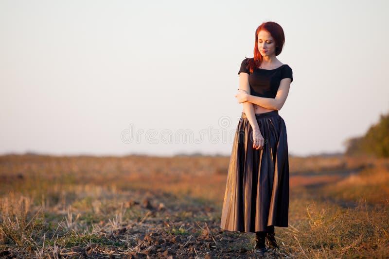 Modnisia redhad dziewczyna w spódnicie zdjęcie stock