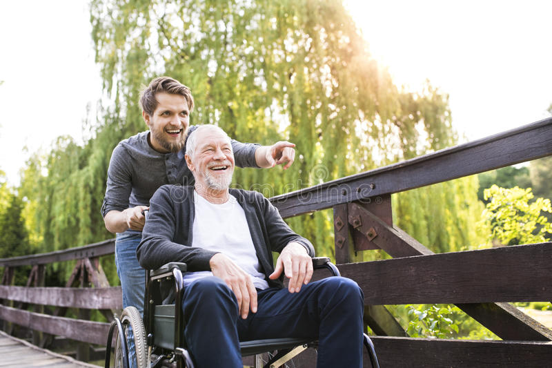Modnisia syna odprowadzenie z niepełnosprawnym ojcem w wózku inwalidzkim przy parkiem obraz royalty free
