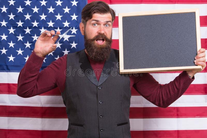Modnisia szyk Brodaci modnisia mienia nożyce i blackboard w klasie Modnisia mężczyzna na flagi amerykańskiej tle modni? obrazy royalty free