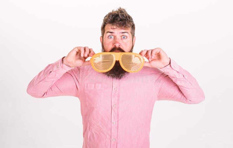 Modnisia zerkanie z gigantów pasiastych okularów przeciwsłonecznych Mężczyzna z brodą i wąsy na zdziwionej twarzy jest ubranym śm obraz royalty free