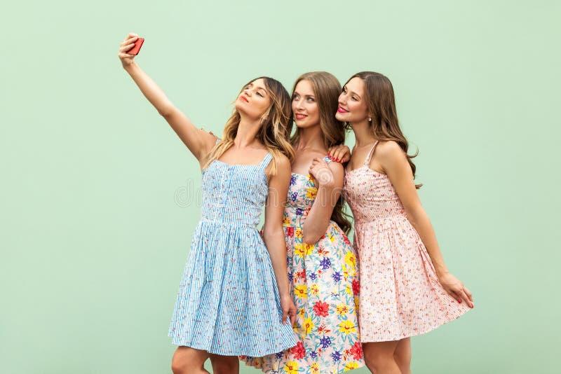 Modnisie trzy przyjaciela w przypadkowej sukni, macking selfie na zielonym tle i zabawę obraz stock