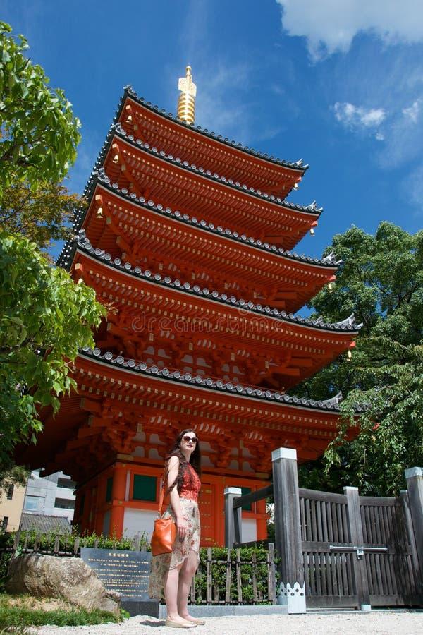 Modny żeński turysta pozuje z czerwoną pagodą w Fukuoka, Japonia Rozjarzona złota iglica i zieleni drzewa obraz stock