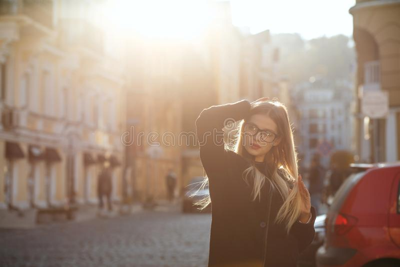 Modny blondynka model z długie włosy jest ubranym żakietem, pozuje w słońca świeceniu Opróżnia przestrzeń zdjęcia royalty free