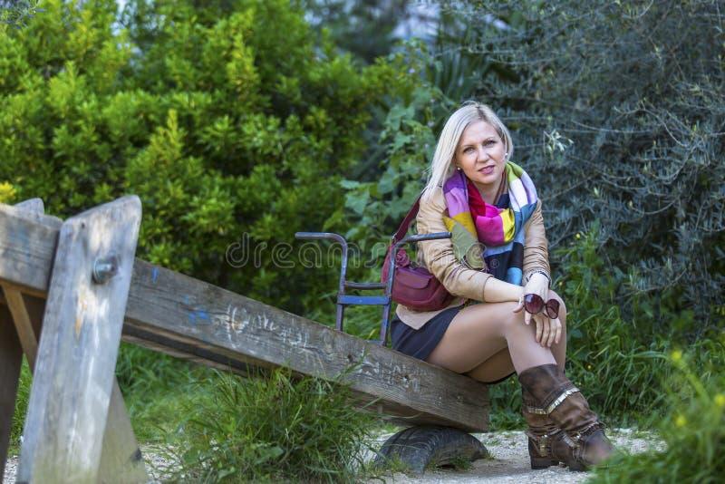 Modny blondynki kobiety obsiadanie w parku na starej drewnianej huśtawce obrazy royalty free