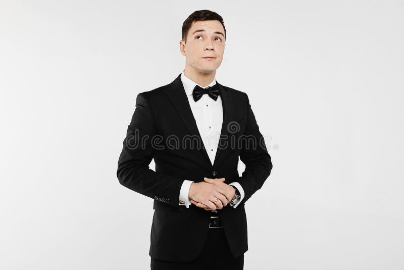 Modny i przystojny młody emocjonalny mężczyzna w białej koszula w eleganckim czarnym kostiumu z łęku krawatem i, odosobnionym prz zdjęcia royalty free