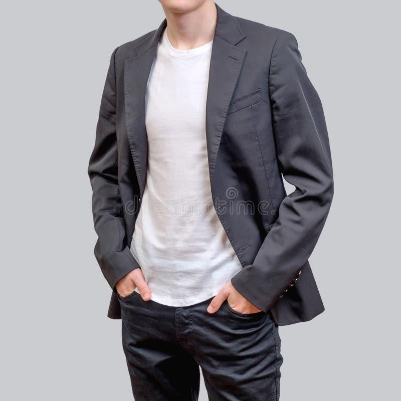 Modny młody człowiek jest ubranym popielatego blezer i ciemnych cajgi stoi przeciw popielatemu tłu, zdjęcia royalty free