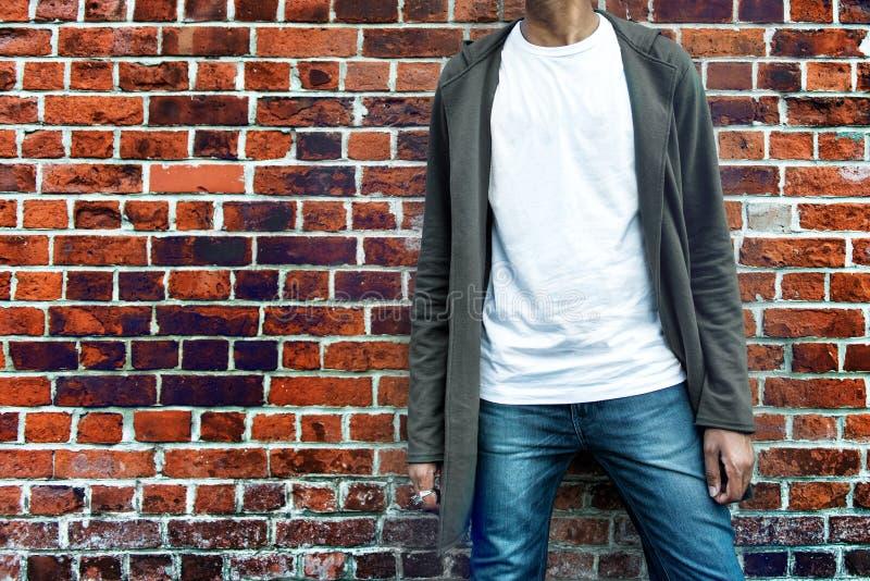 Modny mężczyzna jest ubranym nowożytnego eleganckiego przypadkowego strój z popielatym hoodie, niebieskimi dżinsami i białą koszu obraz royalty free