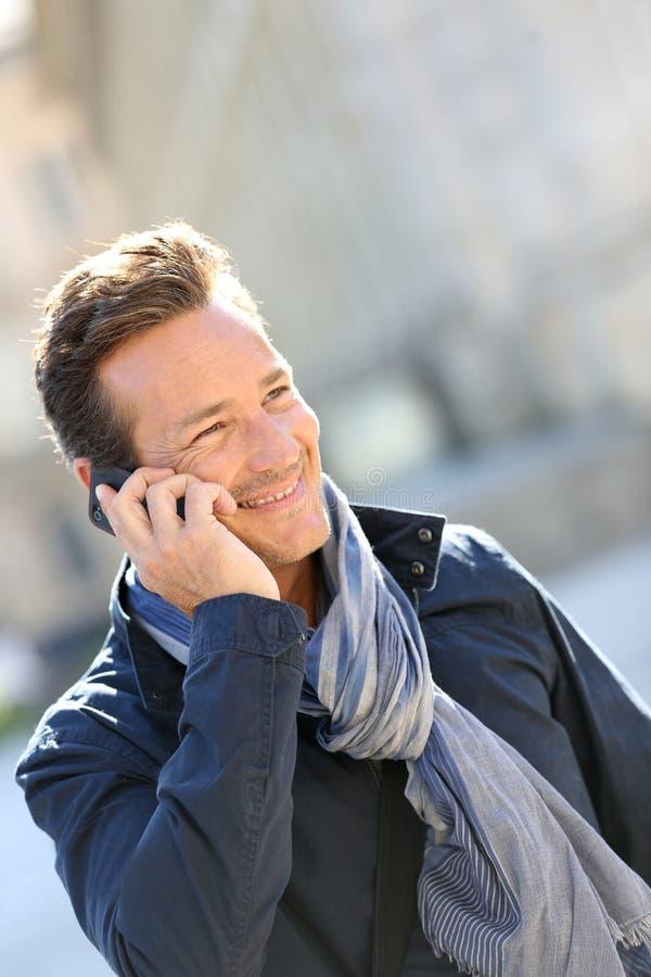 Modny mężczyzna opowiada na telefonie w miasteczku obraz royalty free