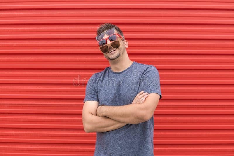 Modny mężczyzna z trzy różnymi rodzajami okulary przeciwsłoneczni na czerwonym tle zdjęcie royalty free