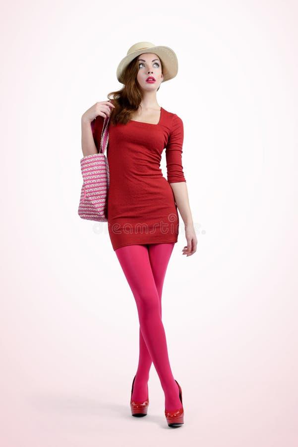 Modny młoda dziewczyna kupujący w czerwieni z torbą obraz stock