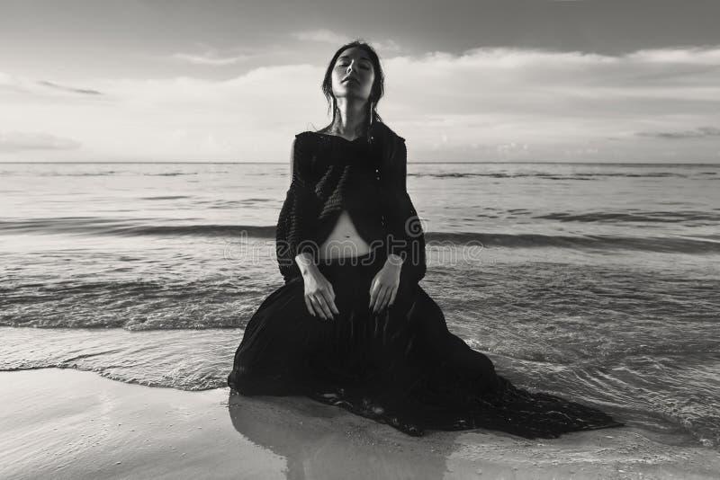 Modny młoda kobieta modela obsiadanie na piasku w wodzie przy zmierzchem fotografia stock