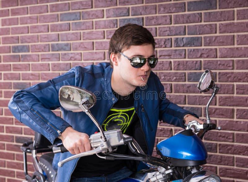 Modny młody człowiek jedzie motocykl w cieniach fotografia stock