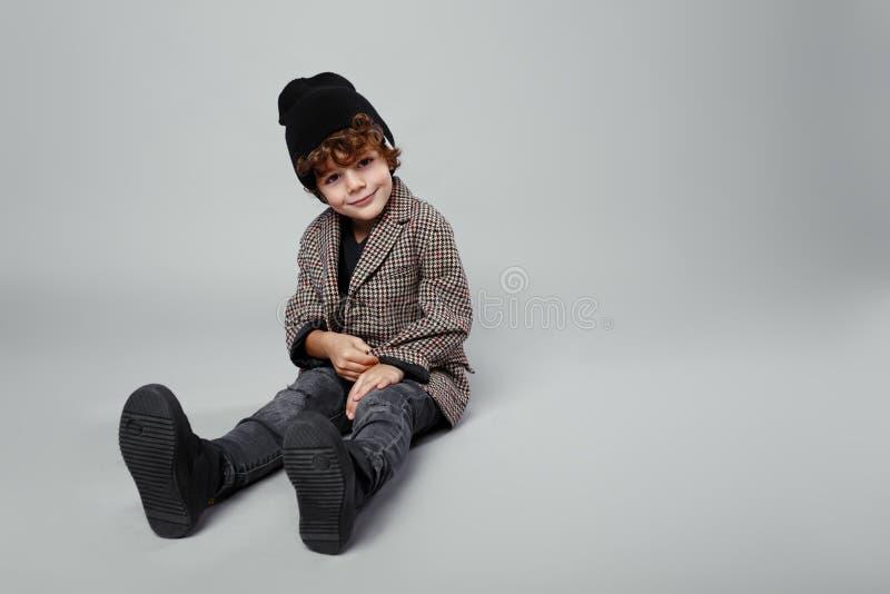 Modny portret śliczna chłopiec sadzał puszek w studiu, być ubranym modny, patrzeje, na białym tle zdjęcie royalty free