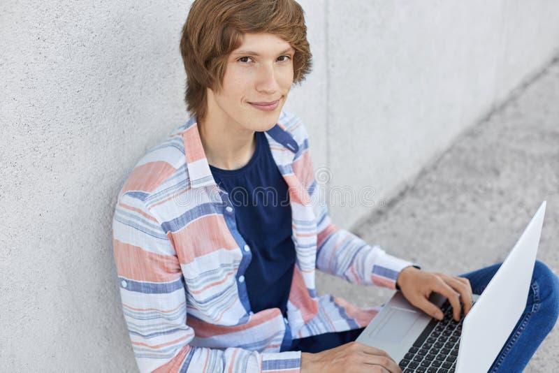 Modny poważny nastolatka obsiadanie na podłogowym mienie laptopie pisać na maszynie coś na klawiaturowy patrzeć w kamerze męski s zdjęcia stock