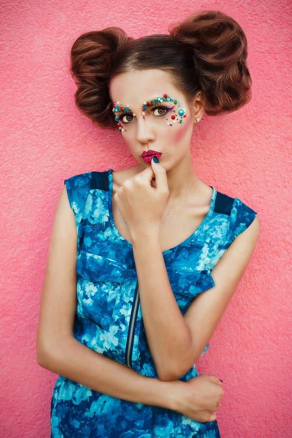 Modny wizerunek modny model z dwa włosów babeczką i kreatywnie fachowym makeup pozuje na różowym tle Kreatywnie robi zdjęcia stock