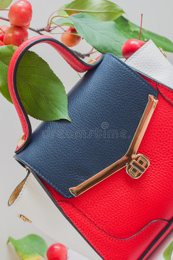 Modny women& x27; s torba od trzy kolorów skóry zakończenie, lekki tło, dekorujący z czerwonymi jabłkami zdjęcia stock