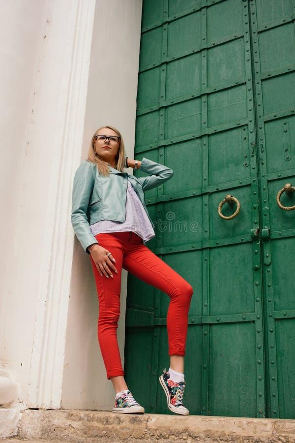 Modnych potomstw wzorcowa dziewczyna w rocznik mody kurtce z cajgami pozuje blisko starych drewnianych drzwi na ulicie obraz stock