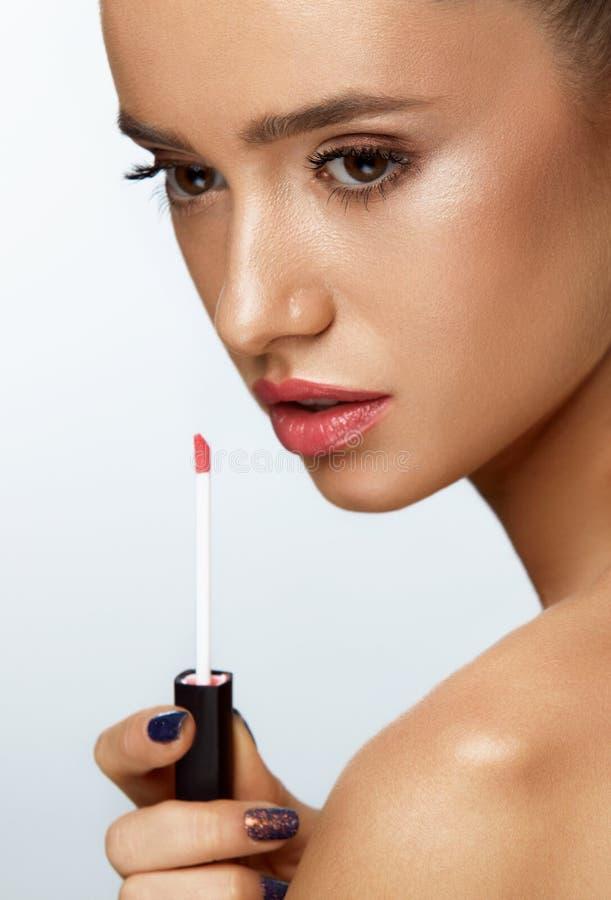 Modo With Beauty Face di modello femminile che applica il balsamo di labbro sulle labbra fotografia stock