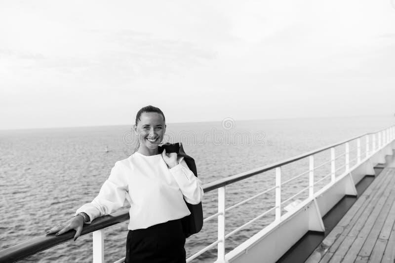 Modo, bellezza, sguardo Donna felice con il rivestimento di affari su fiancata della nave a Miami, S.U.A. Viaggiando per l'affare fotografia stock