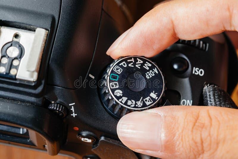 Modo de auto seletor na câmera do dslr com os dedos no seletor fotos de stock royalty free