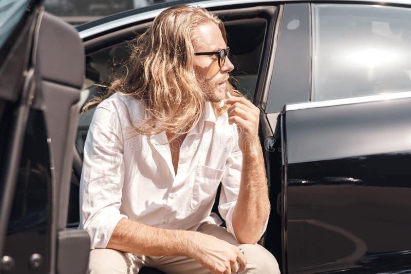 Modo de transporte Hombre con el pelo largo con gafas de sol sentado en un auto eléctrico sosteniendo un cigarrillo mirando a un  foto de archivo