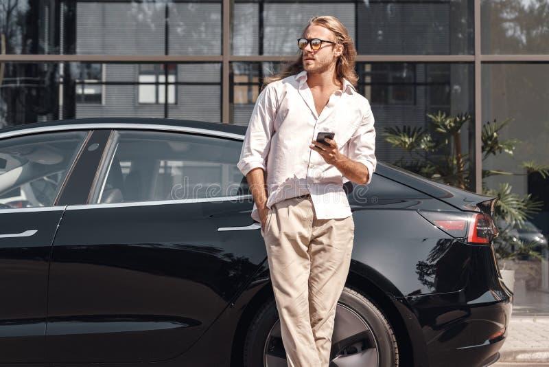 Modo de transporte Hombre con el pelo largo viajando en auto eléctrico inclinándose hacia atrás navegando smartphone mirando a un imagen de archivo