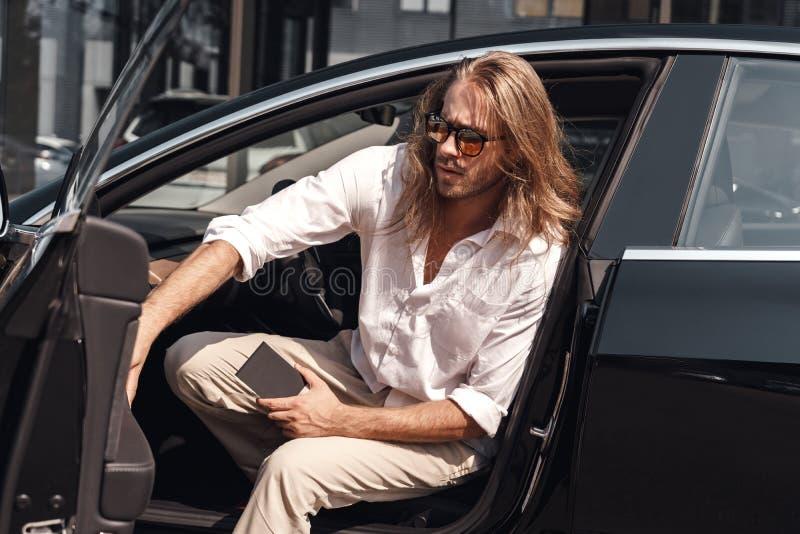 Modo de transporte Hombre con el pelo largo viajando en auto eléctrico saliendo con cartera mirando hacia un lado confiado de cer foto de archivo