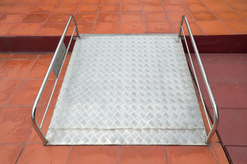 Modo della rampa per i disabili della sedia a rotelle di sostegno Facendo uso della sedia a rotelle fotografia stock