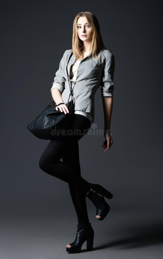 Modo dello studio sparato: bella giovane donna in ghette e rivestimento, con la borsa fotografia stock