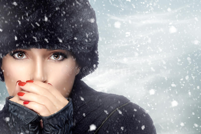 Modo di bellezza di inverno Ragazza in vestiti caldi su una bufera di neve immagini stock