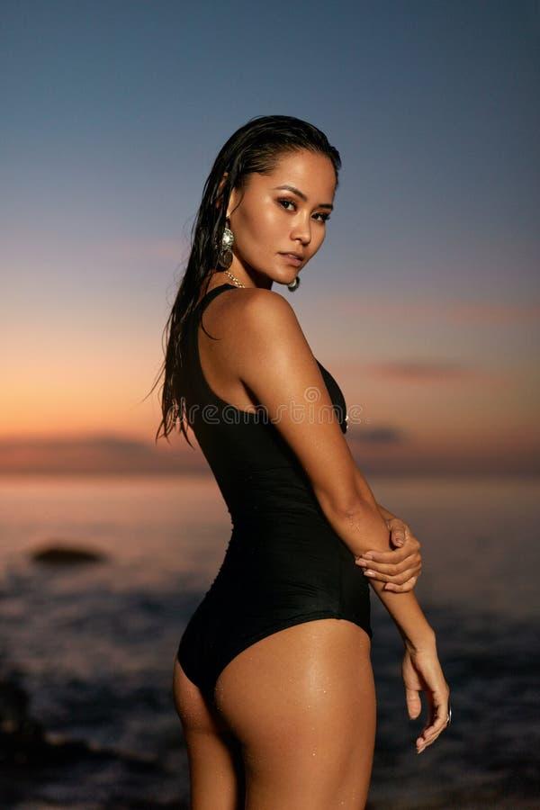 Modo di estate Donna sexy in costume da bagno nero sulla costa di mare fotografia stock