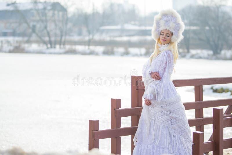 Modo di inverno della donna Ritratto di biondo caucasico sensuale in vestito e bandana bianchi tricottati con pelliccia Kokoshnik fotografia stock libera da diritti