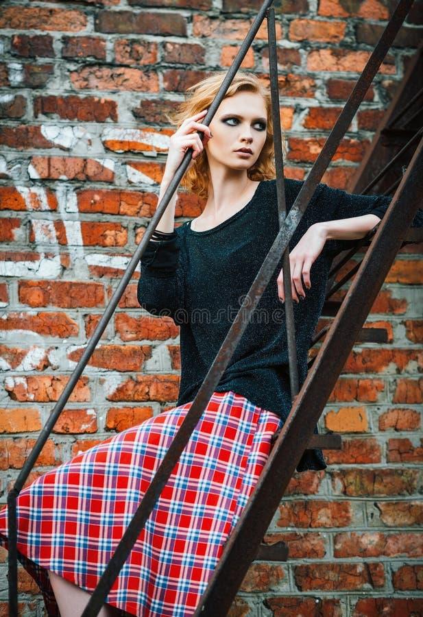 Modo di lerciume: bella ragazza nella condizione della gonna e della blusa di plaid sulle scale immagini stock libere da diritti