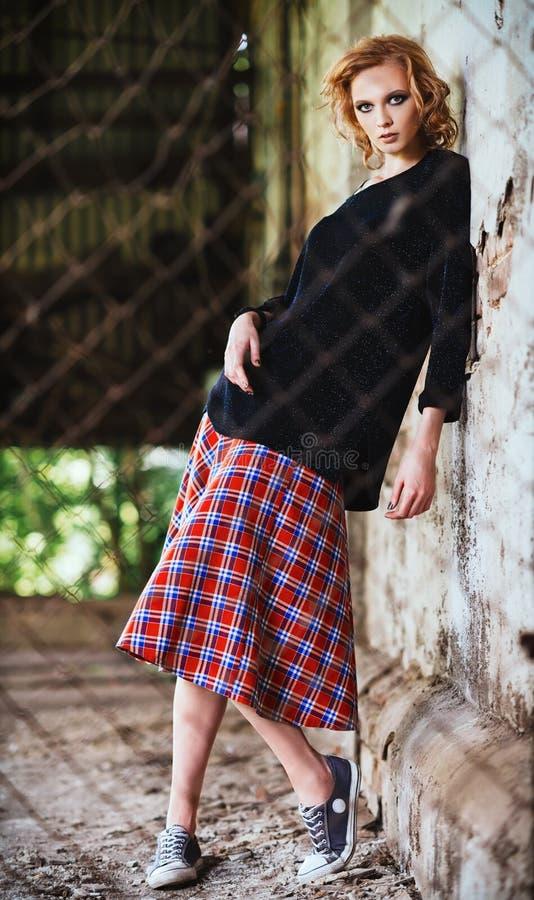 Modo di lerciume: la bella ragazza in gonna a quadretti e blusa sta dietro grata immagine stock libera da diritti