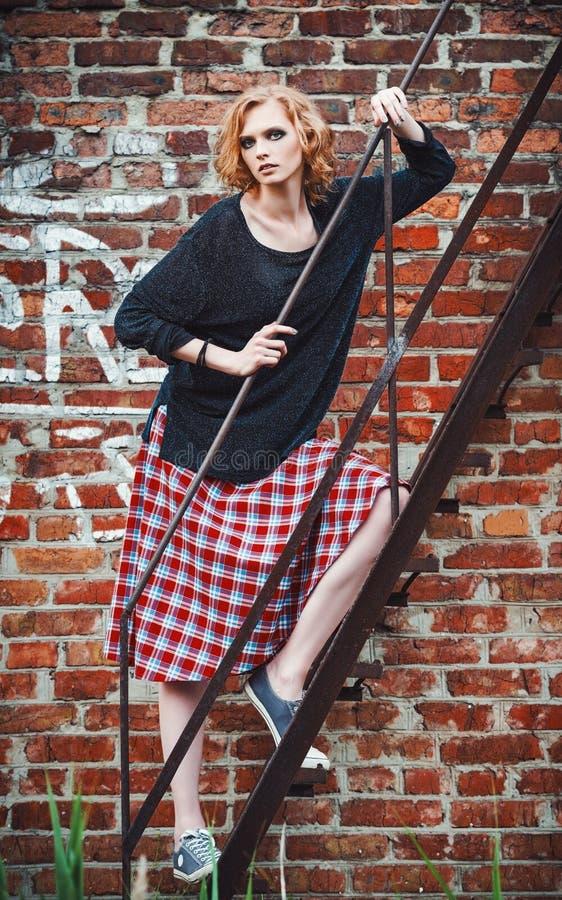 Modo di lerciume: ragazza graziosa in gonna e blusa di plaid che stanno sulle scala immagini stock