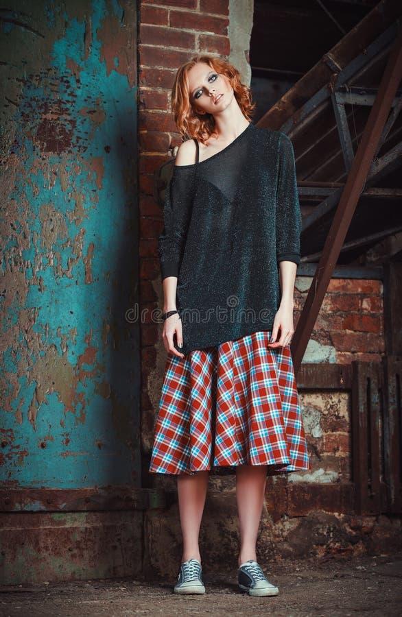Modo di lerciume: ritratto di bella giovane ragazza della testarossa in gonna e maglione di plaid fotografie stock libere da diritti