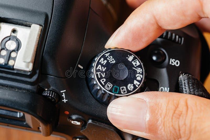Modo di quadrante di avoirdupois sulla macchina fotografica del dslr con le dita sul quadrante immagini stock libere da diritti