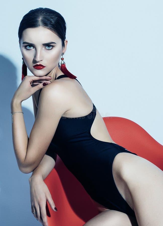 Modo e concetto della gente: la bella donna di modello con le labbra rosse in costume da bagno nero si siede in una sedia immagini stock libere da diritti