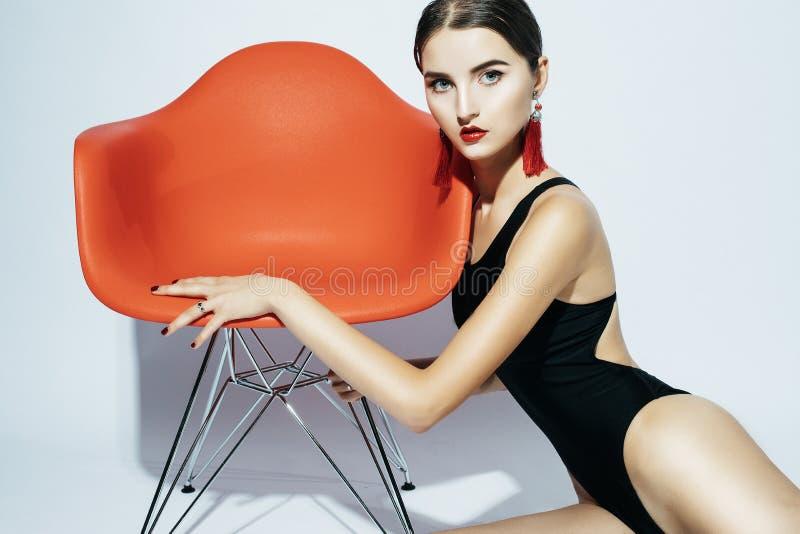 Modo e concetto della gente: la bella donna di modello in costume da bagno nero si siede in una sedia fotografie stock