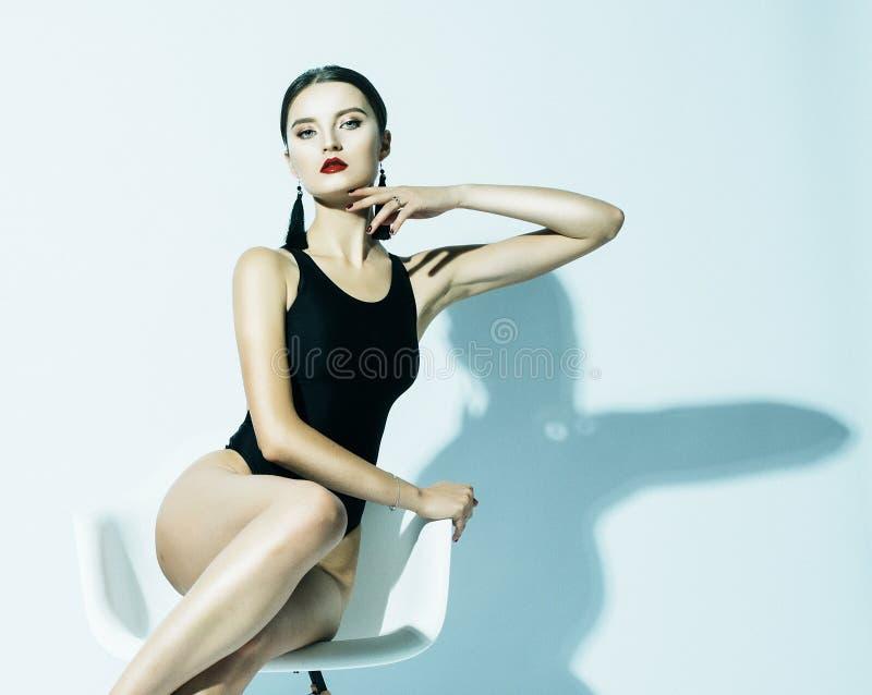 Modo e concetto della gente: la bella donna di modello in costume da bagno nero si siede in una sedia fotografia stock