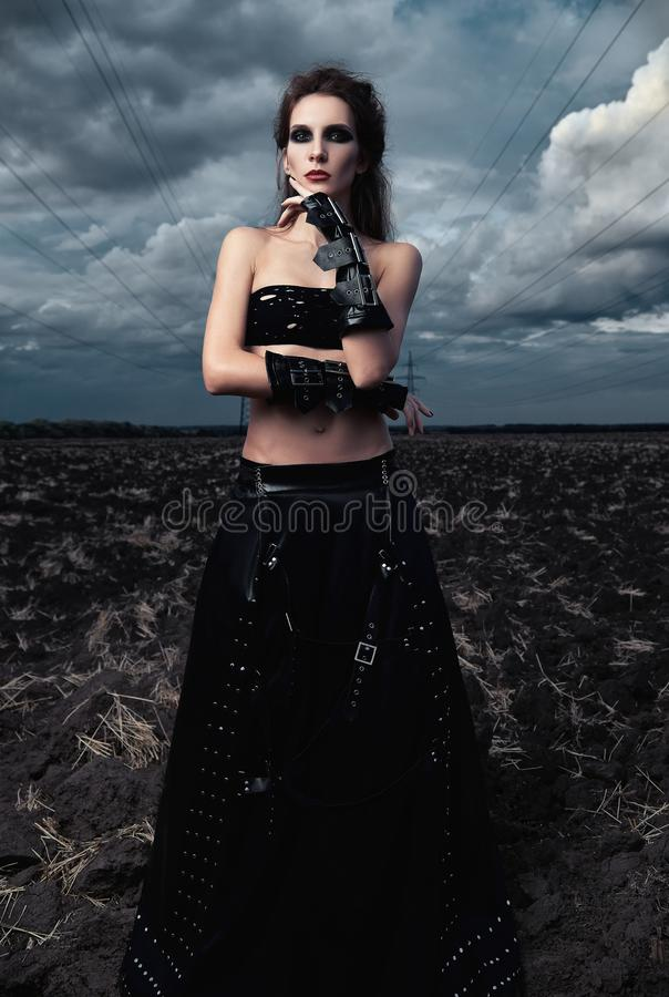 Modo informale: giovane ragazza esile splendida del goth vestita in gonna ed in guanti di cuoio neri Ritratto all'aperto nel camp fotografia stock