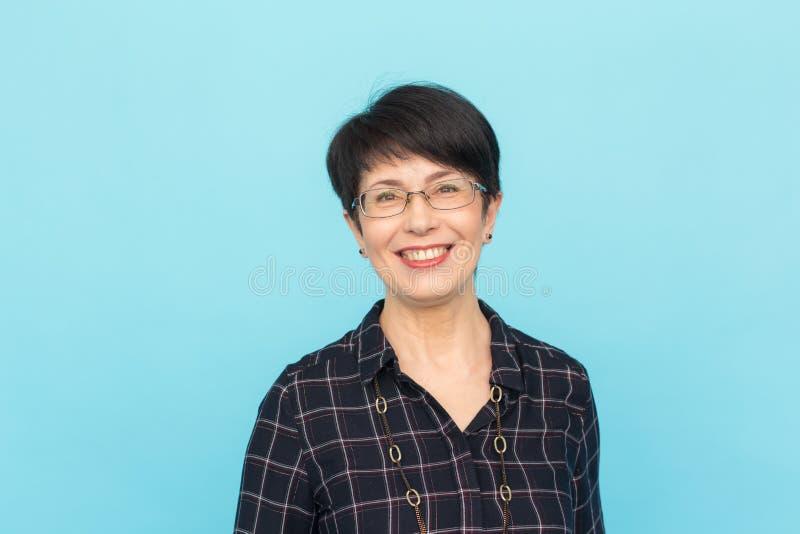 Modo, la gente e concetto di stile - bei occhiali d'uso mezzo vecchi della donna che ridono sul fondo blu fotografie stock