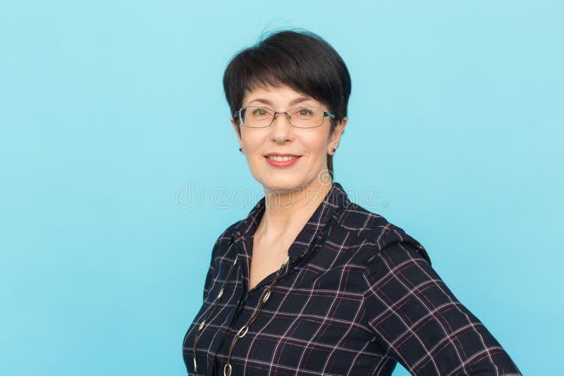 Modo, la gente e concetto di stile - bei occhiali d'uso mezzo vecchi della donna che ridono sul fondo blu con la copia fotografia stock libera da diritti