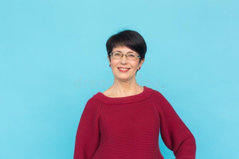 Modo, la gente e concetto di stile - bella donna mezzo vecchia in maglione e vetri rossi su fondo blu fotografia stock