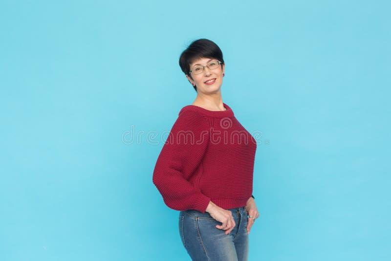 Modo, stile e concetto della gente - donna adulta in maglione rosso con le sue mani in tasche su fondo blu con la copia fotografia stock libera da diritti