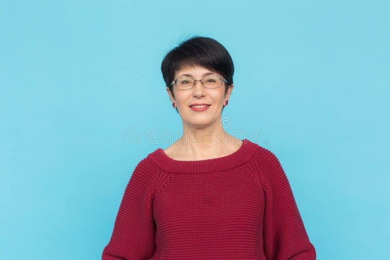 Modo, stile e concetto della gente - donna adulta in maglione rosso su fondo blu immagine stock